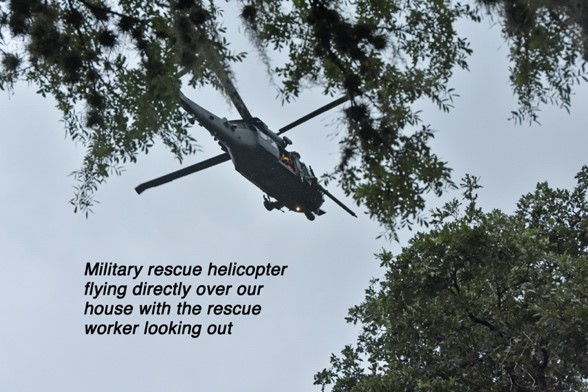 """Military rescue helicopter flying directly over our house with the rescue worker looking out"""