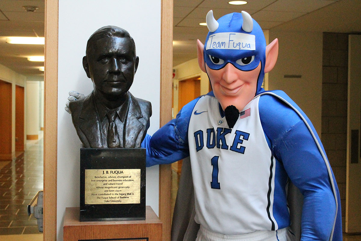 Blue Devil standing with J.B. Fuqua statue